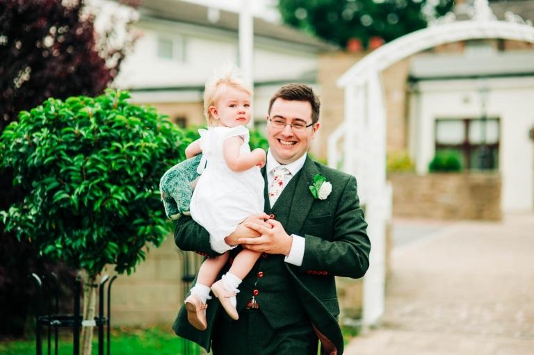 Groom holds flower girl as he walks to the pavillion