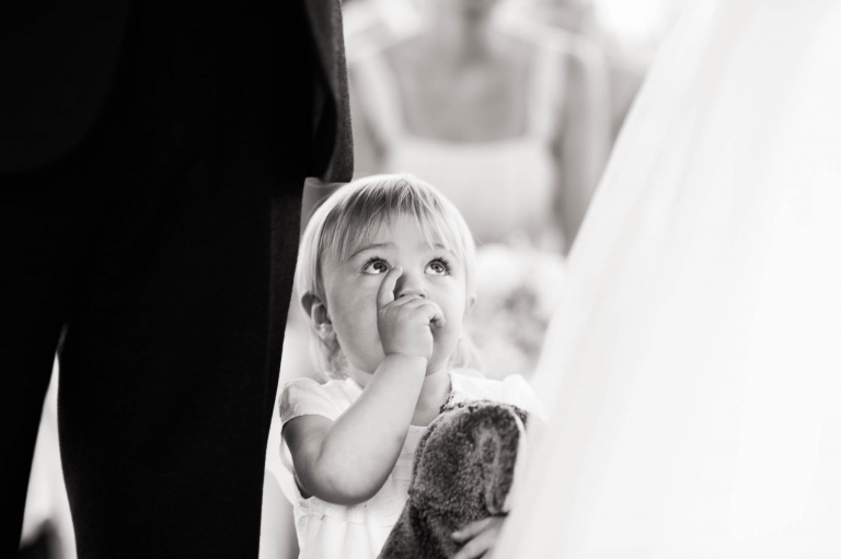 Flower girl looks up at the bride and groom during the wedding ceremony