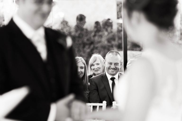Guests smile at the bride and groom during the cremony