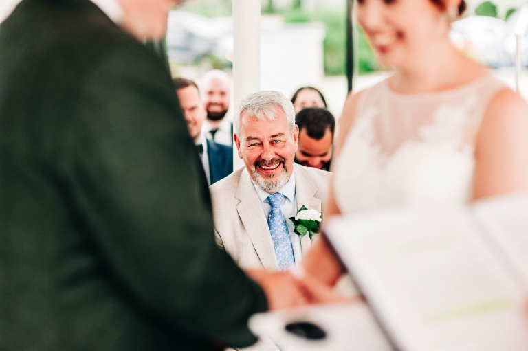 Father of the bride looking very happy as the happy couple exchange wedding rings