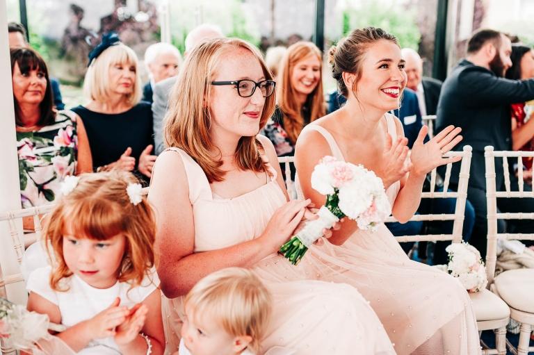 Bridesmaids clap the happy couple