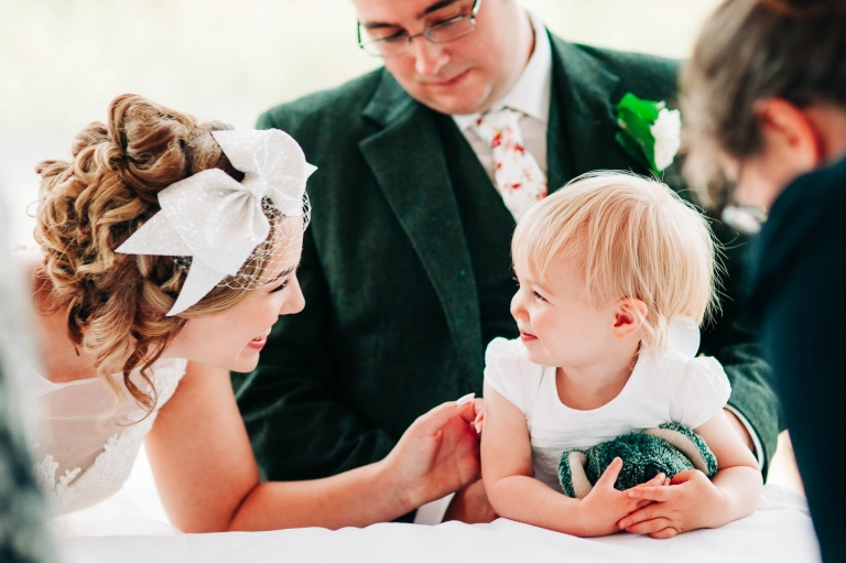 Bride and flower girl smile at each other