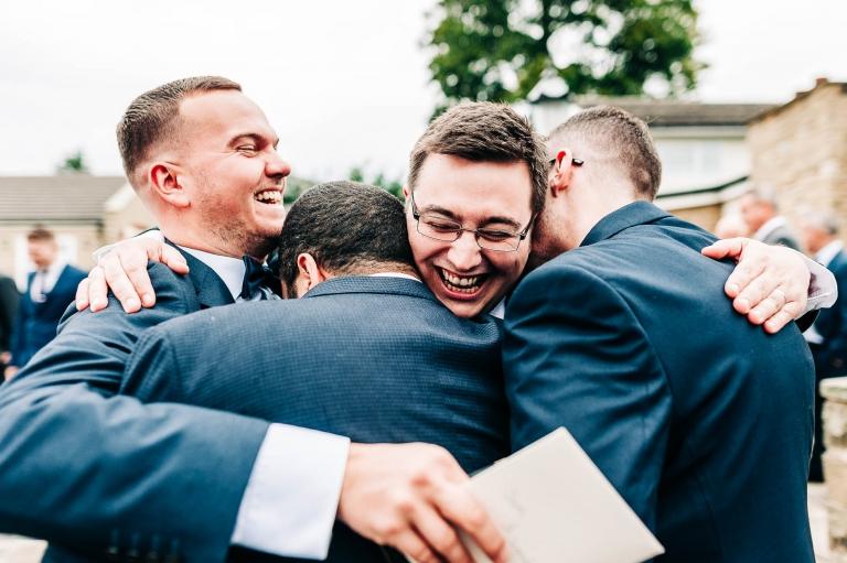 Groom hugs a few friends