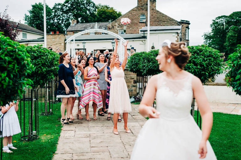 Bridesmaid catches the flowers in the bouquet toss
