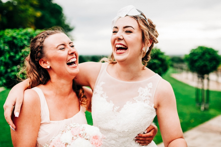 Bridesmaid and bridesmaid hold each other laughing
