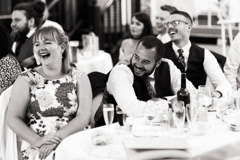 Guests laugh during the father of the bride's speech