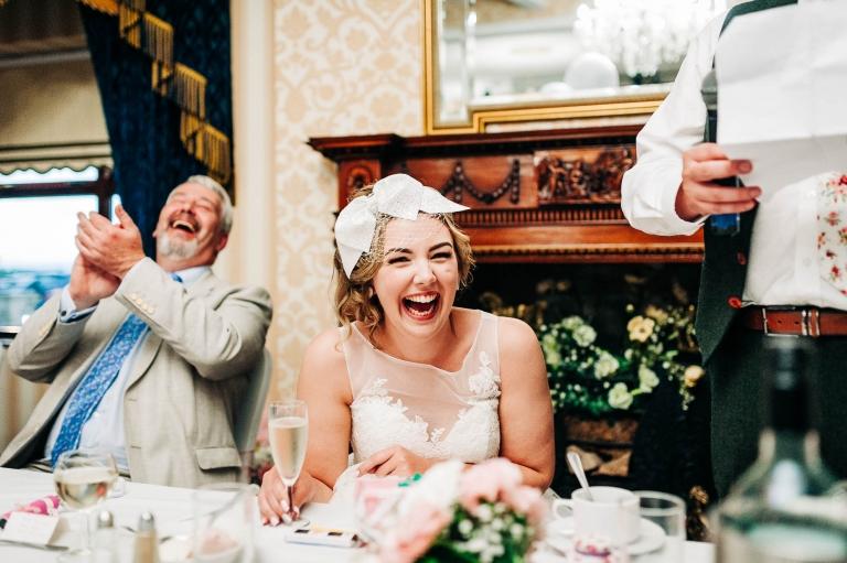 Bride laughs at Groom's joke during his speech