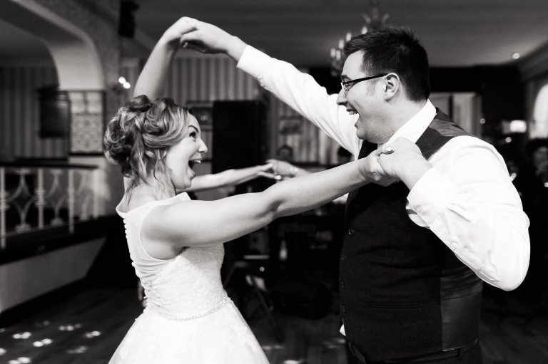 Bride and groom Laugh together as they dance