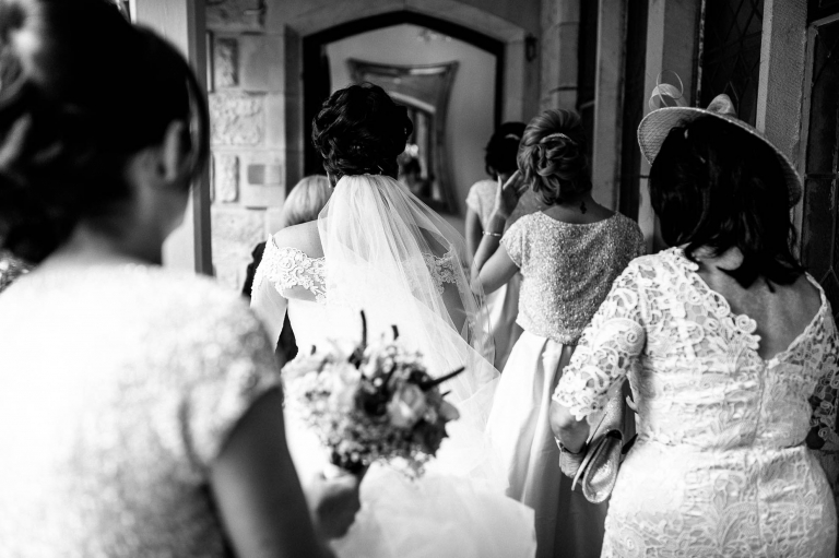 bride walks into West Tower with her bridesmaids