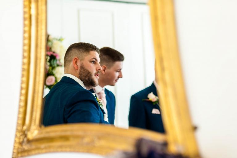 groom looks down the aisle