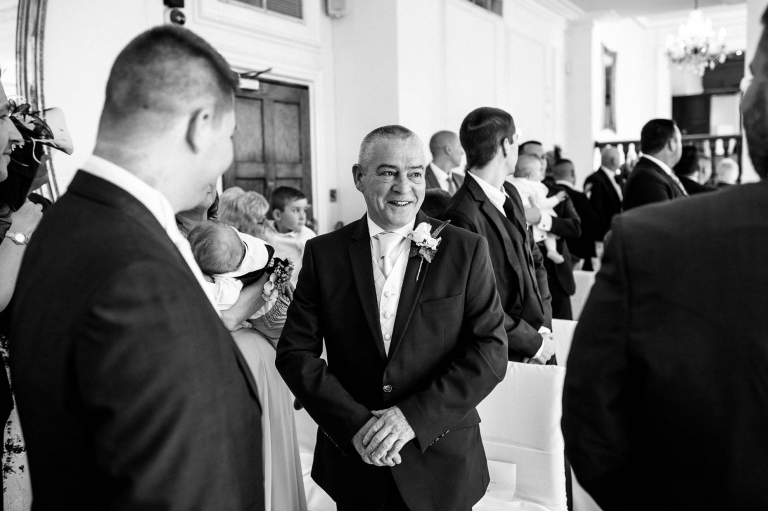father of the groom smiles at groom