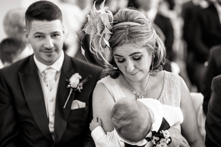 mother of the bride looks lovingly at grandson