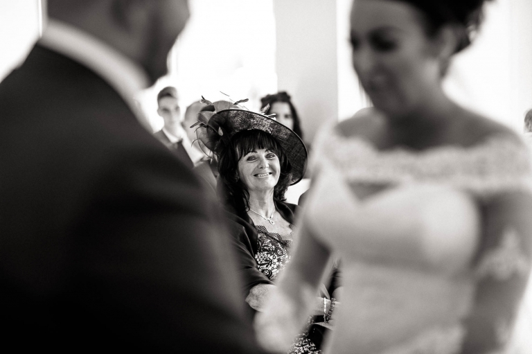 brides aunt looks on and smiles during the wedding ceremony
