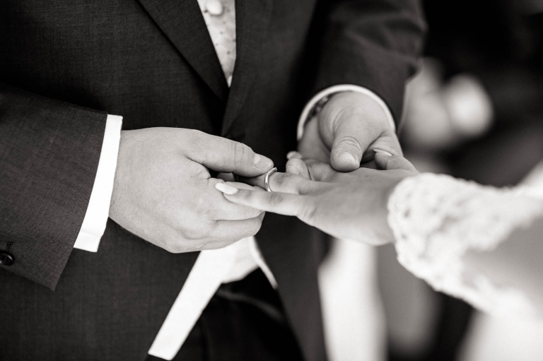 groom places the ring on brides finger