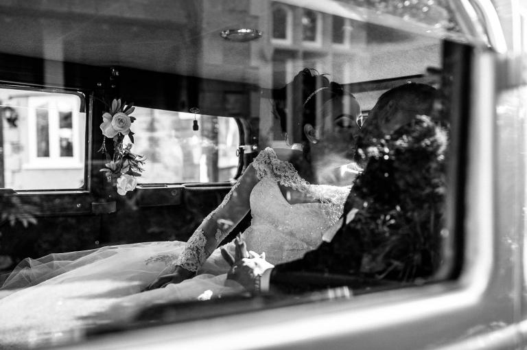 bride and groom kiss in wedding car
