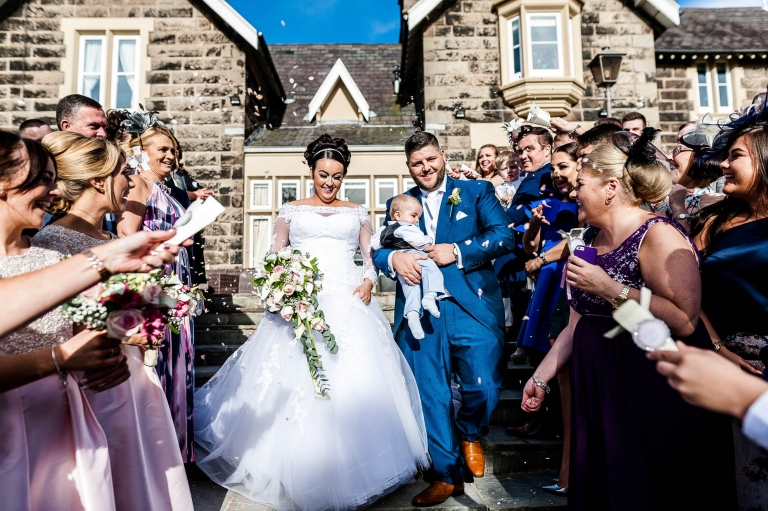 guests shower bride and groom with confetti