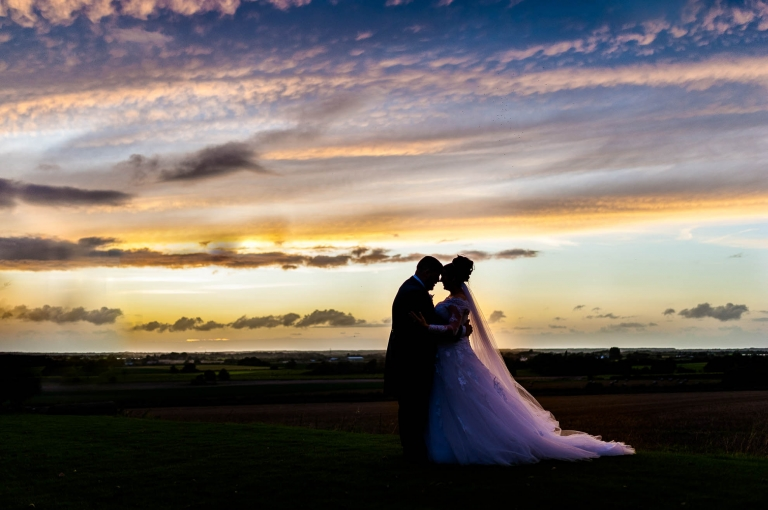 bride and groom hold each other with sunset