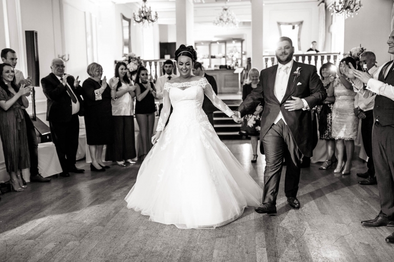 bride and groom walk onto the dance floor for first dance