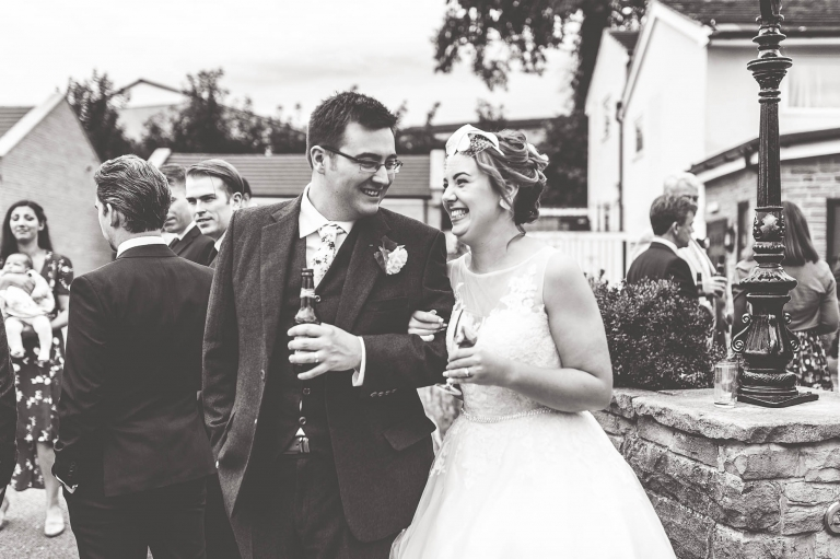 Bride and groom share a joke during the drinks reception