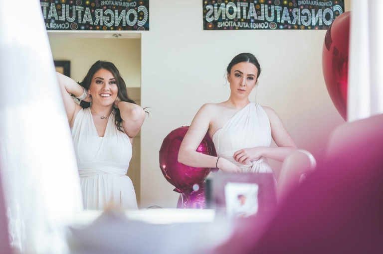 Bridesmaids put their dresses on during bridal preparations