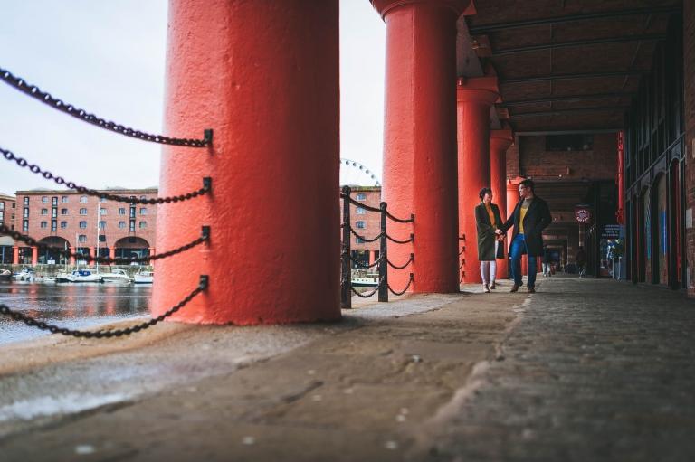 couple walk along Albert Dock Liverpool