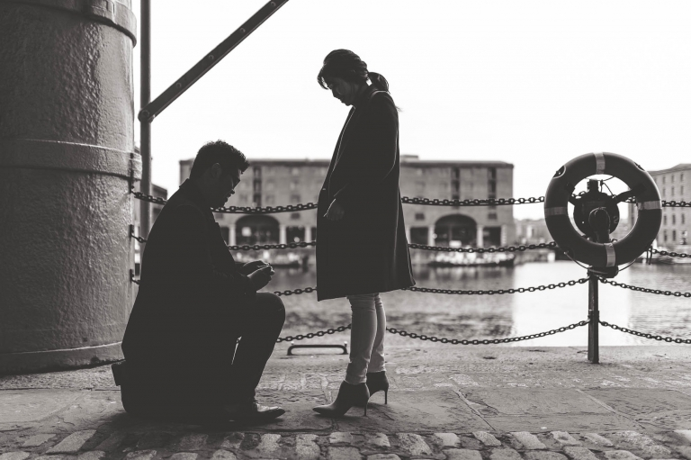 fiance gets down on one knee to propose to girlfriend