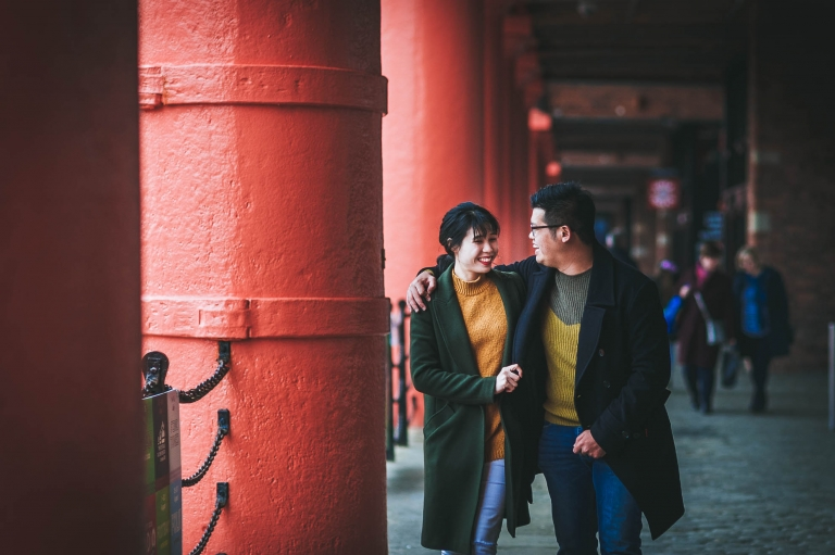 Engaged couple walk in Albert dock
