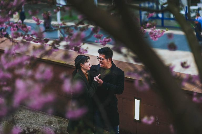 Engaged couple share a joke as they walk along