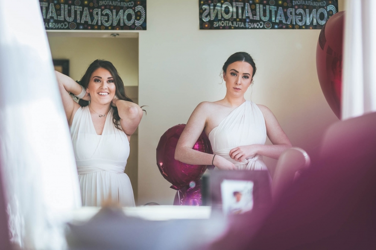bridesmaids look in mirror getting ready