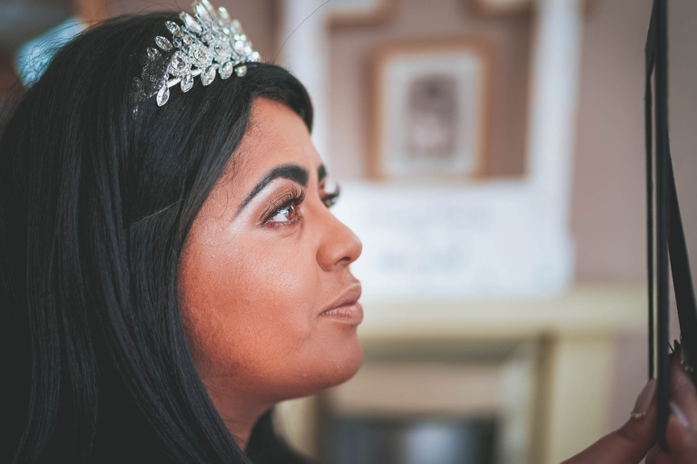 bride inspects her make up in the mirror