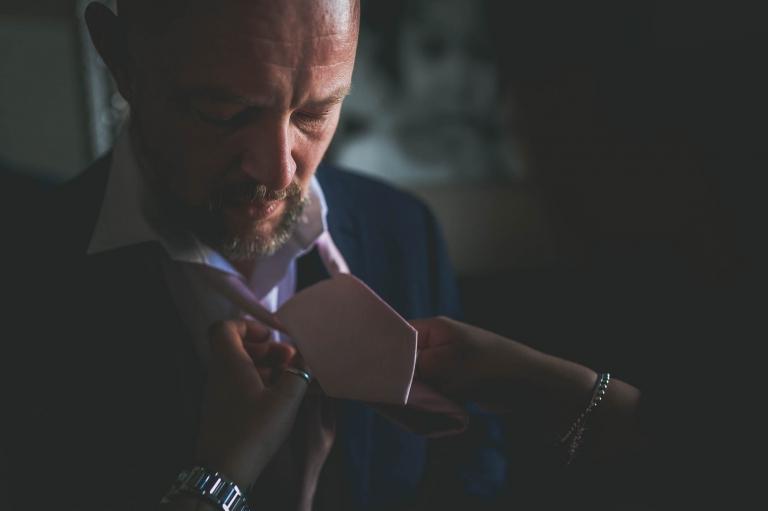 usher having his necktie put on
