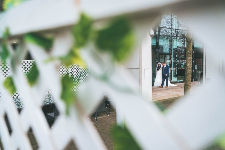 bride and groom shot through fence