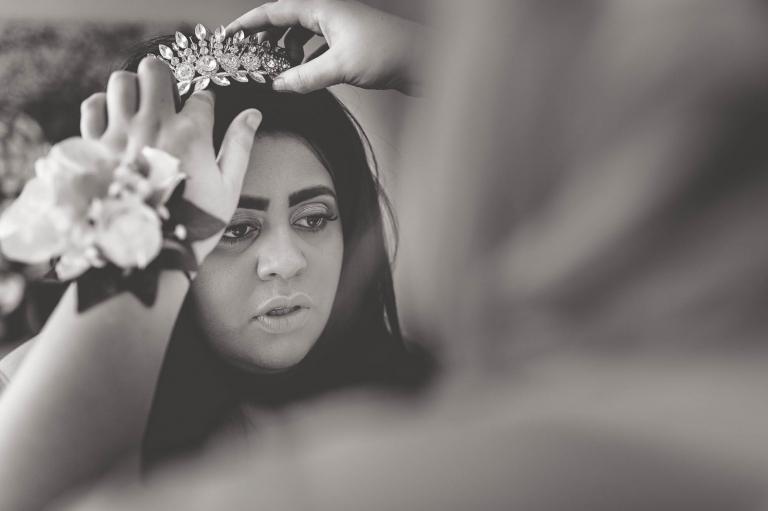 bridesmaid fits tiara on bride