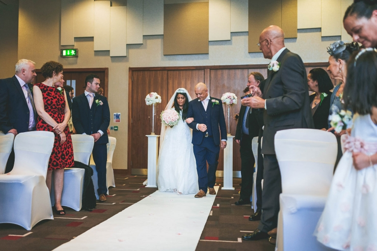 bride walks up aisle with father of the bride