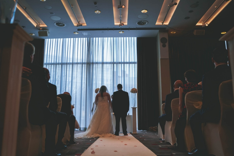 view of bride and groom from back of the ceremony room