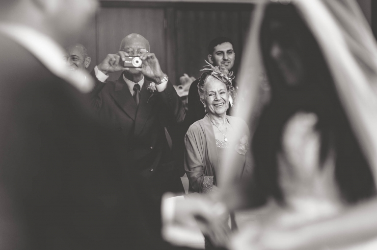 grandmother of the bride smiles at the couple