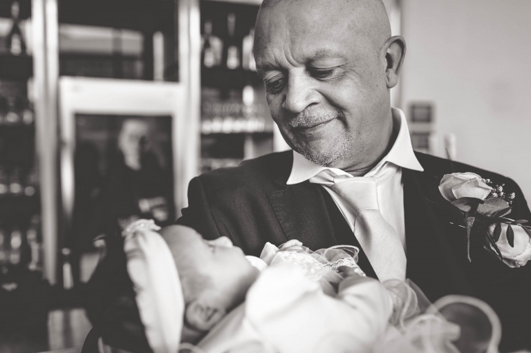 father of the bride holds his grandchild