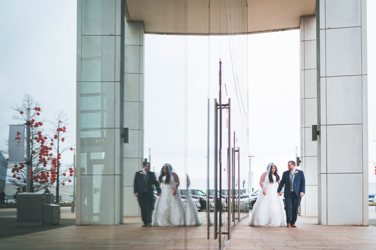 bride and groom walk reflection in mirror of Hilton liverpool