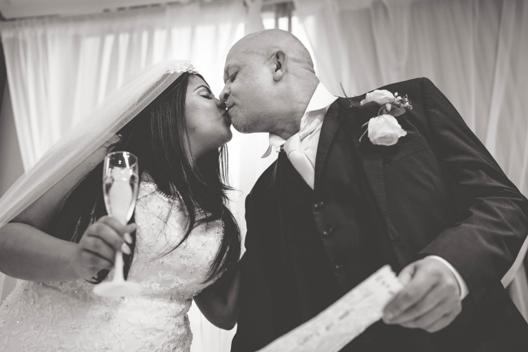 father of the bride gives bride a kiss