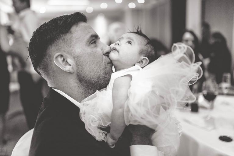 dad kisses baby daughter