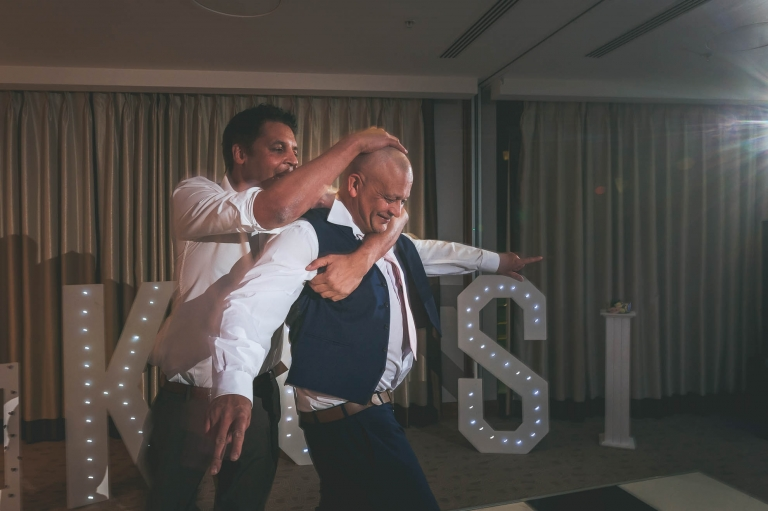 man wrestles playfully with father of the bride