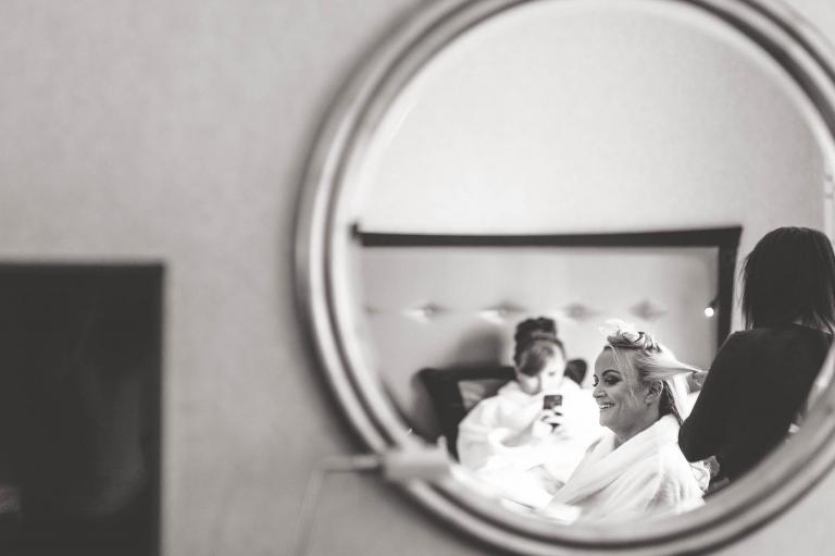 bride in mirror getting her hair styled