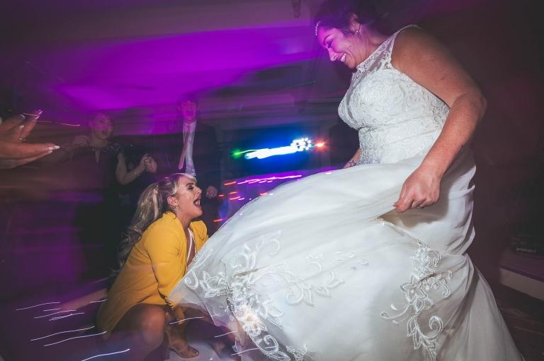 guest adjusts brides dress