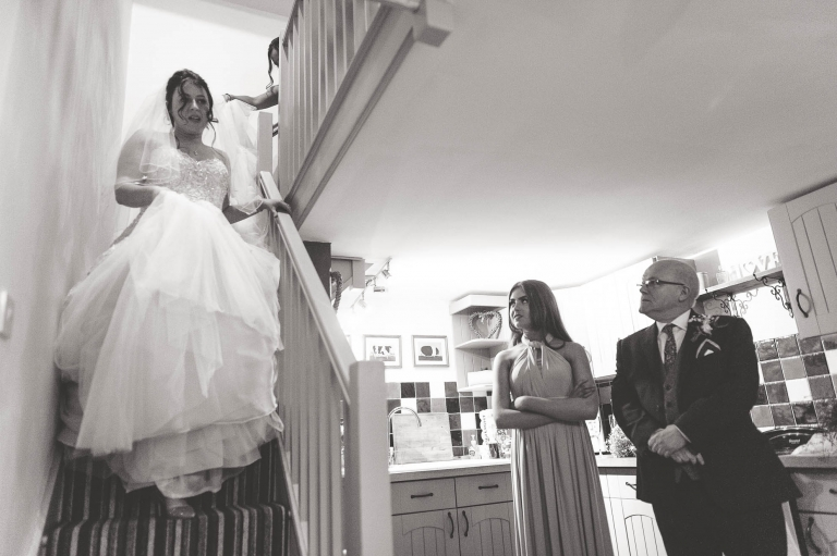 bride walks down stairs in her wedding dress