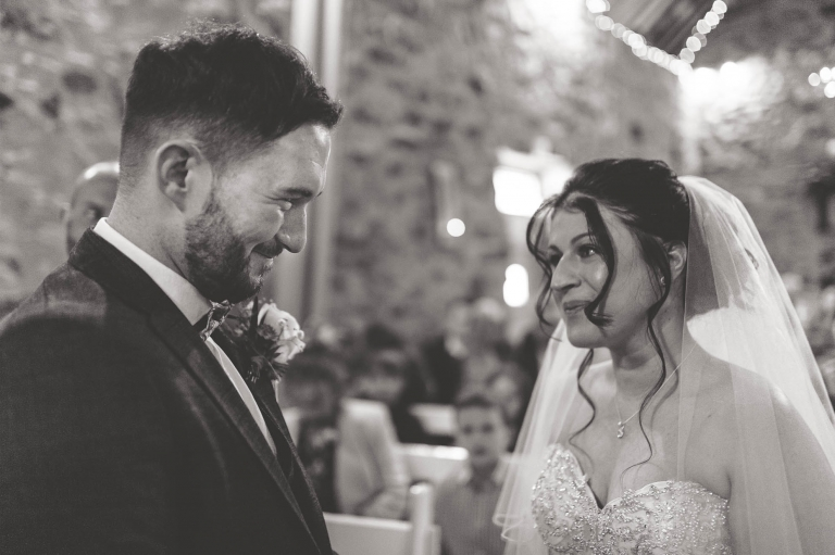 bride and groom smile at each other during wedding vows