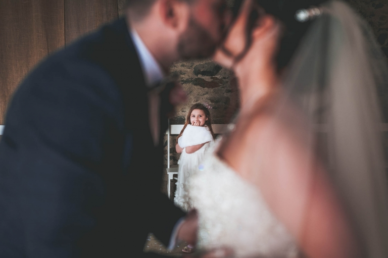 Flower girl giggles as she looks at bride and groom kissing