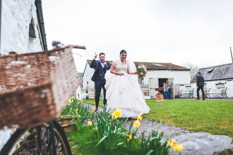 Brid e and groom walk best the barn