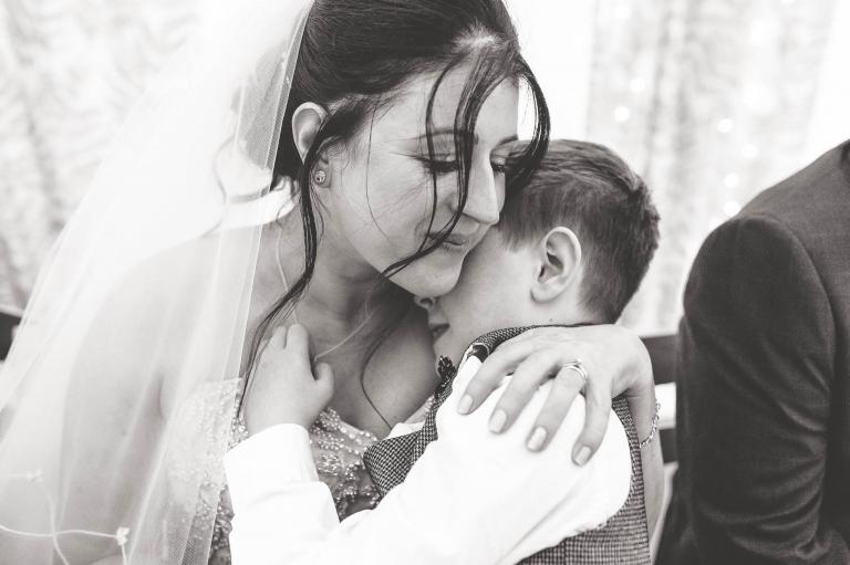 Bride gives son a hug