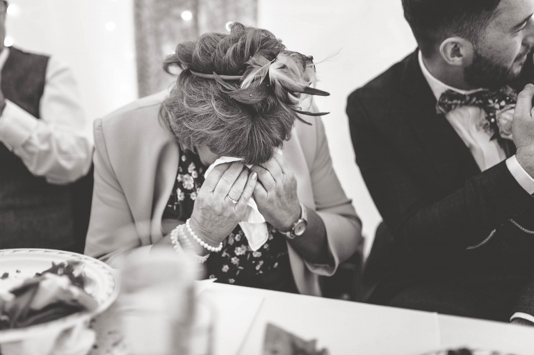 Mother of the groom wipes away a tear