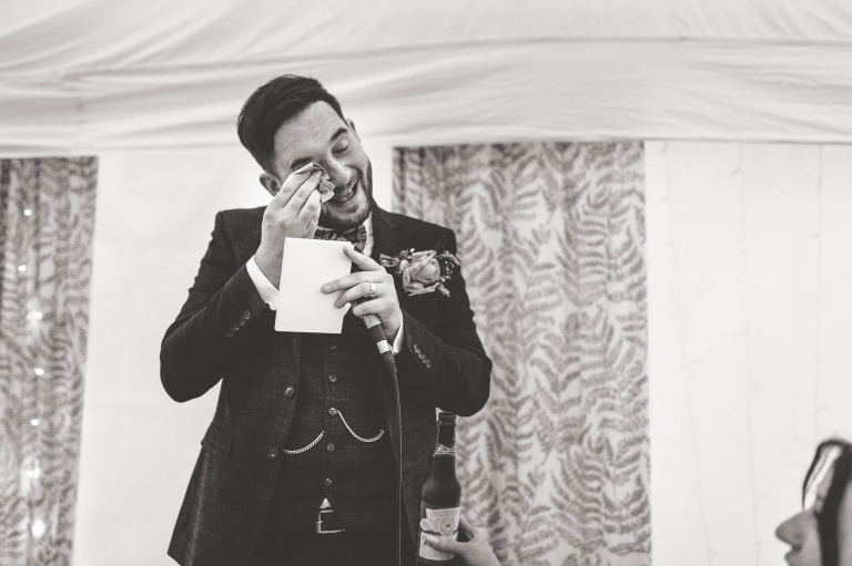 Groom wipes away a tear as he gives his speech